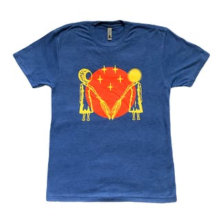 This is an image of a blue, short sleeve t-shirt. It has a crew neck and a two color, red and yellow logo on it. The logo has a red circle with an illustration of two women extending barley stalks inward toward one another.