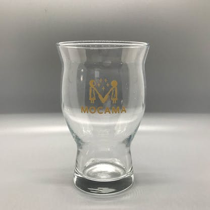 This is a picture of a glass with a slim base and a wide, flared out top. It has a printed logo in gold which contains the words Mocama and an illustration of two women holding barley stalks.