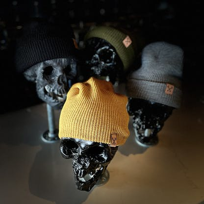 Photo of our beanies in all 4 colors: yellow, gray, black, and green.