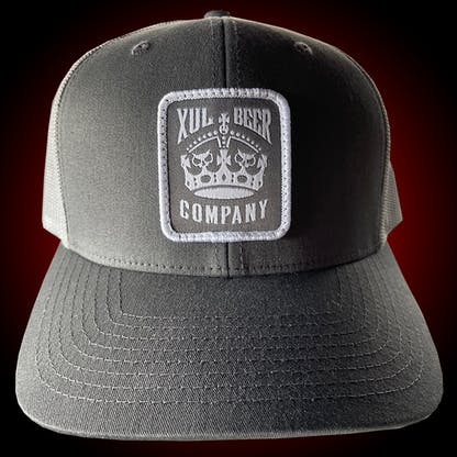 Gray trucker hat with our crown logo on a gray patch. Front view.