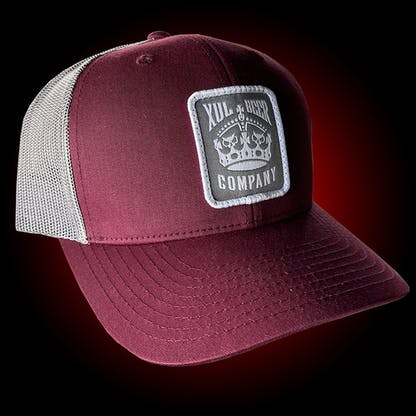 Maroon trucker hat with our crown logo on a gray patch. Side view