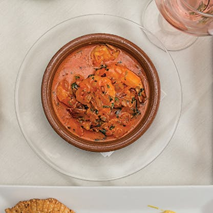 Seafood in a ceramic dish with a creamy orange sauce and parsley sprinkled on top. The bowl is on a clear glass plate on a white linen table cloth next to a glass of rose wine.