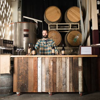 Photo of David Teixeira, winemaker for Lusu Wines wearing a blue plaid longsleeve shirt behind an old reclaimed wood bar with bottles of Lusu wine featured on the counter in a winemaking environment with fermentors and oak barrels on racks.